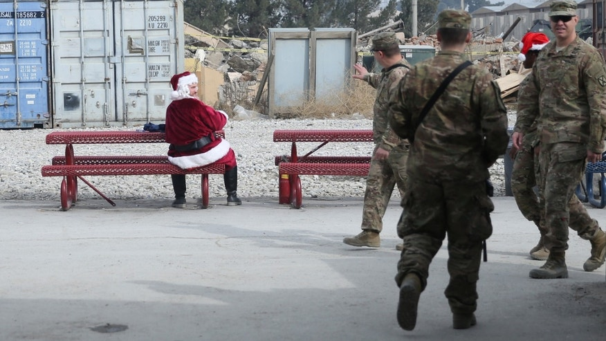 A U.S. soldier dressed as Santa Claus waves to fellow troop  son Christmas day at the U.S. air base in Bagram, north of Kabul, Afghanistan, Friday, Dec. 25, 2015. (AP Photo/Massoud Hossaini)