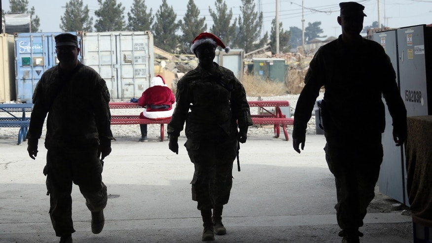U.S. soldiers walk past a fellow soldier wearing a Santa Claus costume during Christmas day celebrations at Bagram Air Field, north of Kabul, Afghanistan, Friday, Dec. 25, 2015. (AP Photo/Massoud Hossaini)