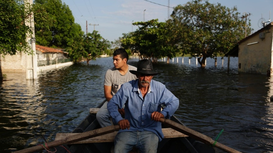 Victor Ferreira, displaced by flooding, rows through the streets in Asuncion, Paraguay, Wednesday, Dec. 23, 2015.