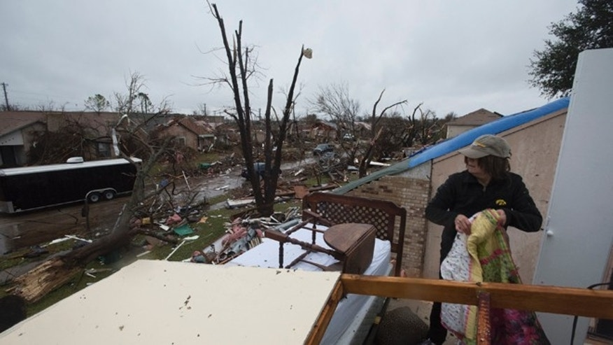 Delores Downard salvages items from her son's house in Rowlett, Texas, Sunday, Dec. 27, 2015, the morning after it was struck by a tornado. At least 11 people died and dozens were injured in apparently strong tornadoes that swept through the Dallas area and caused substantial damage this weekend. (AP Photo/Rex C. Curry)