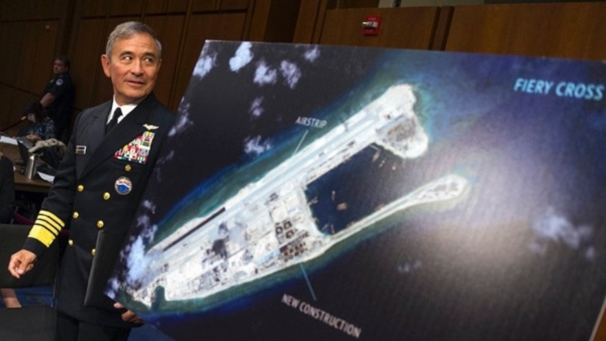 FILE - In this Sept. 17, 2015, file photo, Adm. Harry B. Harris, Jr., commander of U.S. Pacific Command, walks past a photograph showing an island that China is building on the Fiery Cross Reef in the South China Sea, as he prepares to testify on Capitol Hill in Washington before the Senate Armed Services Committee hearing on maritime security strategy in the Asia-Pacific region.