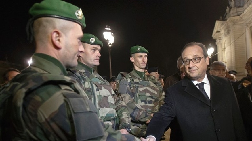Dec. 31, 2015: France's President Francois Hollande, right, shakes hands with a foreign legionnaire as he visits the security measures at the Champs Elysees in Paris.