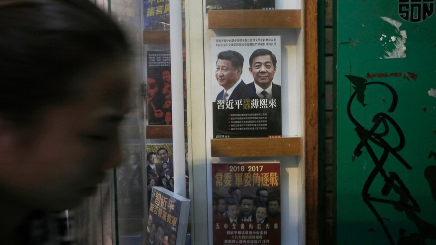 Jan 3. 2016: A woman walks past a book featuring a photo of Chinese President Xi Jinping, left, and former Politburo member and Chongqing city party leader Bo Xilai on the cover, at the entrance of the closed Causeway Bay Bookstore.  (AP Photo/Vincent Yu)