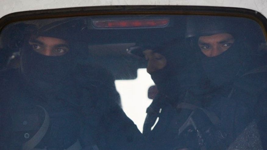 Jan. 5, 2016: Indian military commandos look from inside a vehicle at the Indian air force base in Pathankot, India.