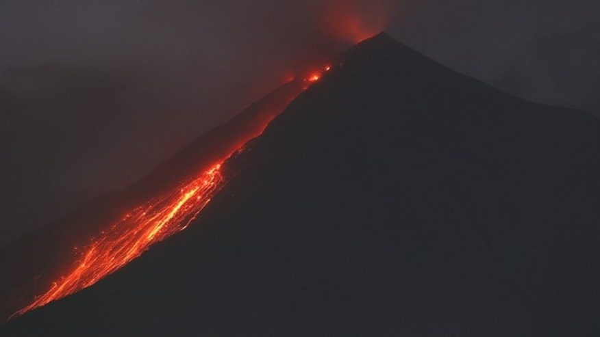 The Volcano of Fire releases lava, seen from San Juan Alotenango, Guatemala, Monday, Jan. 4, 2016. Guatemalan authorities are on alert after the country's Volcano of Fire erupted in dramatic fashion on Sunday. (AP Photo/Moises Castillo)