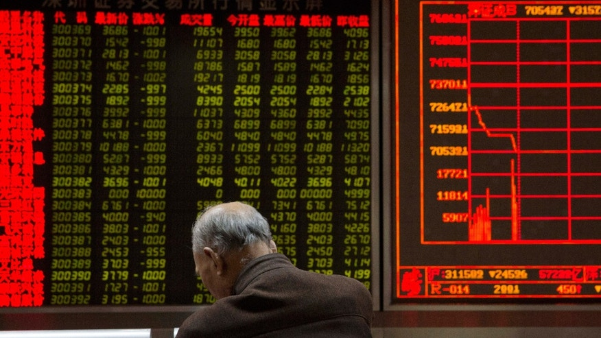 Jan. 7, 2016: An investor rests near a display board showing the plunge in the Shanghai Composite Index at a brokerage in Beijing, China