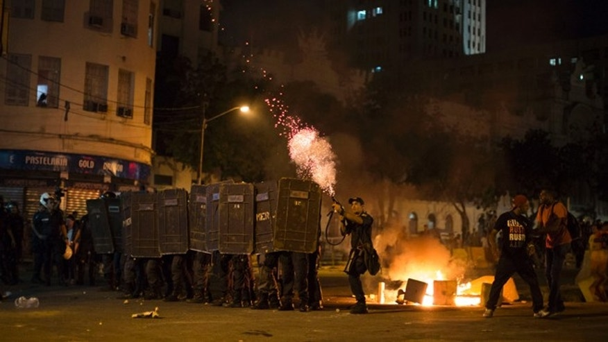 A police officer fires tear gas toward protesters during a march against bus fare hikes in Rio de Janeiro, Brazil, Friday, Jan. 8, 2016. The march, which is also taking place in other Brazilian capitals, began peacefully in downtown Rio de Janeiro but turned violent. (AP Photo/Felipe Dana)
