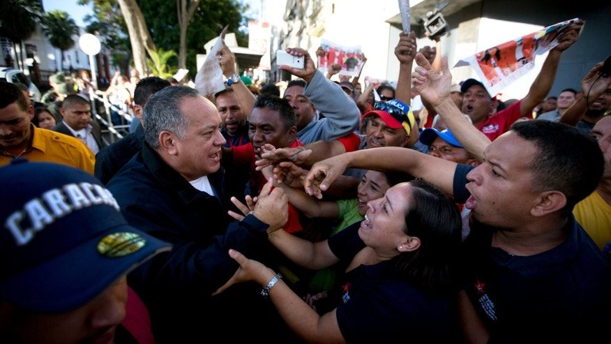 Diosdado Cabello greets government supporters as he leaves the legislature in Caracas, Jan. 6, 2016.