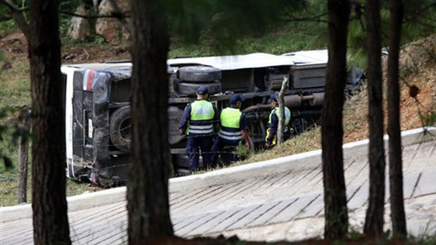This photo courtesy of El Heraldo de Honduras newspaper shows a bus on its side along the highway between the town of San Juancito and the capital city of Tegucigalpa, Honduras, Wednesday, Jan. 13, 2016.