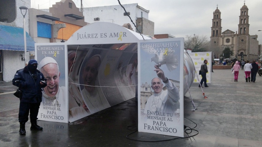 In this photo taken Jan. 5, 2016, a police officer patrols in Juarez, Mexico, in front of a Pope Francis installation advertising the pope's upcoming visit the city. Juarez, on Mexico's northern border across from El Paso, Texas, is the last stop in the Pope's schedule 5-day trip to Mexico and officials on both sides of the border are preparing for the visit between Feb. 12-17.  (AP Photo/Russell Contreras)