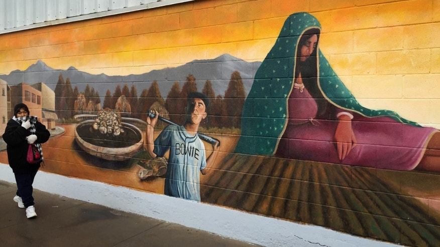 Inn this photo taken, Jan. 5, 2016, a woman walks past a mural of the Virgin of Guadalupe and border life in the Segundo Barrio of El Paso, Texas. Officials in El Paso, and Juarez, Mexico, are preparing for a Pope Francis visit to the Mexican city next month. Juarez, on Mexico's northern border across from El Paso, is the last stop in the pope's schedule 5-day trip to Mexico between Feb. 12-17.  (AP Photo/Russell Contreras)