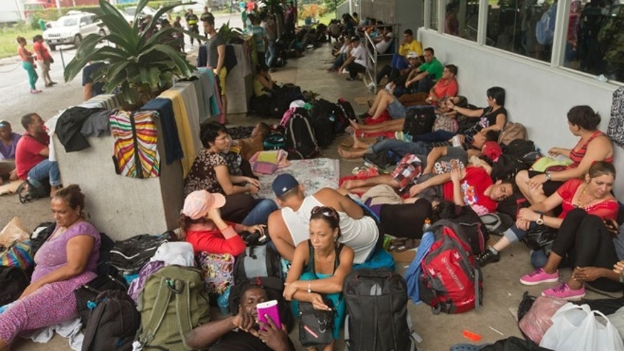 Cuban migrants sit outside a Costa Rican immigration building on the border with Nicaragua, in Peñas Blancas, Costa Rica, after Nicaragua closed its border to all Cuban migrants, leaving them stuck in Costa Rica. (AP Photo/Esteban Felix, File)