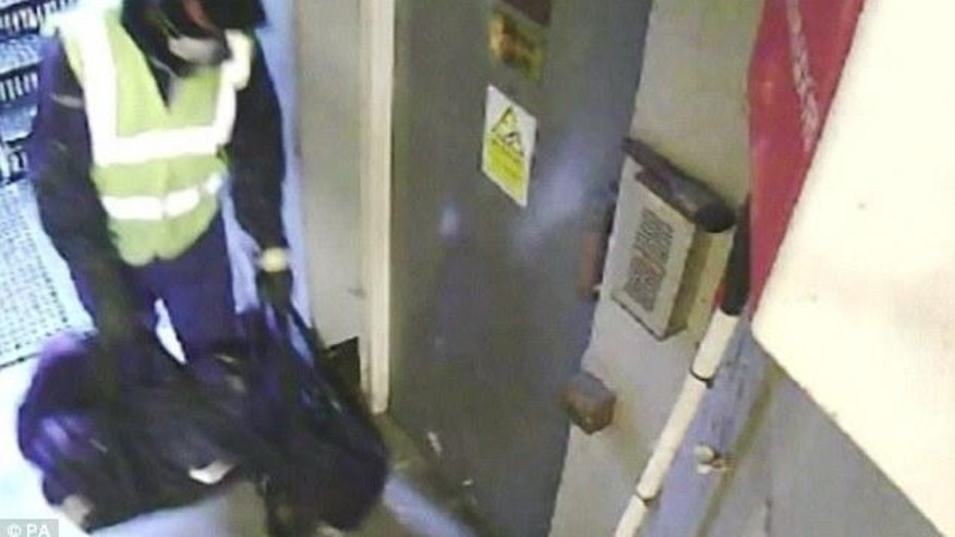 Surveillance image of a suspect at the fire escape with tools.
