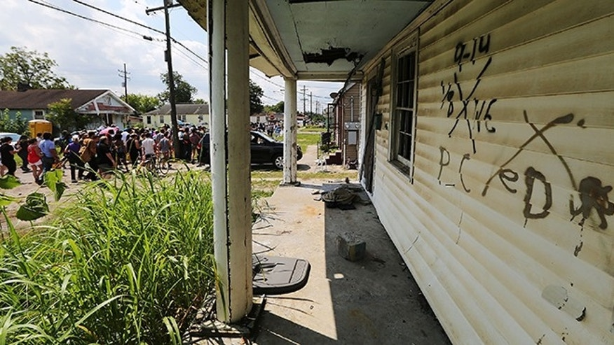 NEW ORLEANS, LA - AUGUST 29:  Revelers march past an abandoned home still marked by rescue markings in the Lower Ninth Ward during a second line parade marking the 10th anniversary of Hurricane Katrina on August 29, 2015 in New Orleans, Louisiana.  A levee breach along the Industrial Canal in the Lower Ninth Ward devastated the area with massive flooding in the aftermath of Hurricane Katrina.  (Photo by Mario Tama/Getty Images)