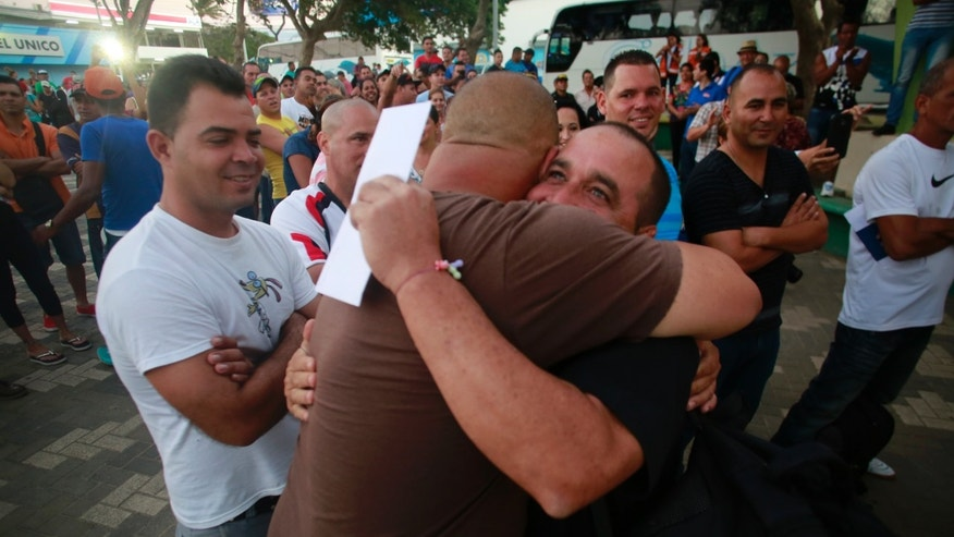 Cuban migrants hug goodbye in La Cruz, Costa Rica, Tuesday, Jan. 12, 2016.