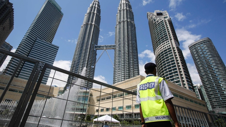 Dec. 31, 2015: A security guard patrols in front of Malaysia's landmark buildings, Petronas Twin Towers, ahead of the New Year's celebration in Kuala Lumpur, Malaysia.