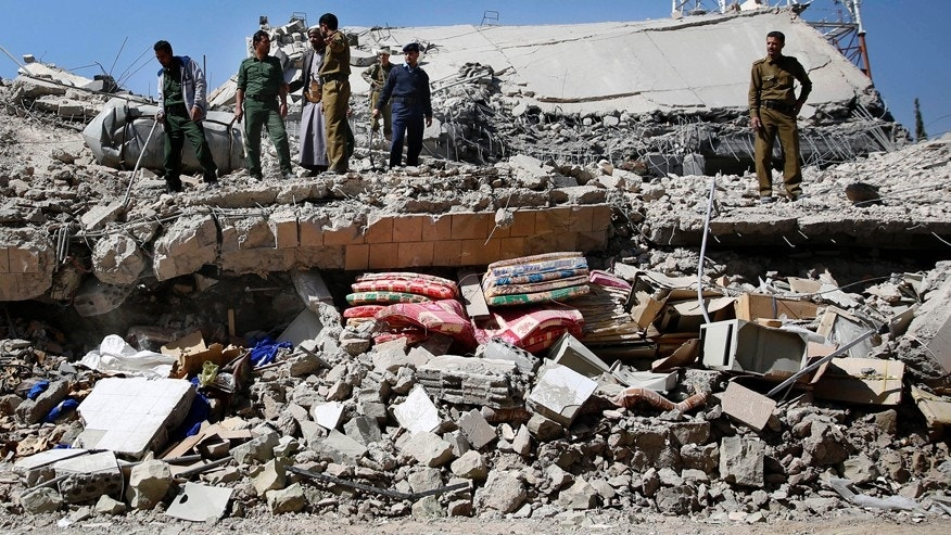 Jan. 18, 2016: Policemen gather at the site of a Saudi-led airstrike on the police headquarters in Sanaa, Yemen.