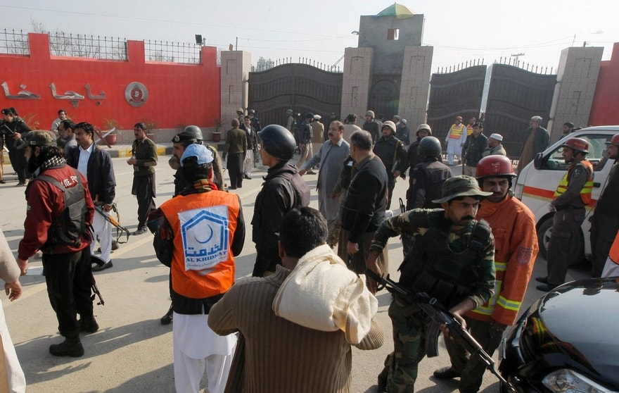 Pakistani troops and rescue workers gather at the main gate of Bacha Khan University in Charsadda town, some 35 kilometers (21 miles) outside the city of Peshawar, Pakistan, Wednesday, Jan. 20, 2016. Gunmen stormed Bacha Khan University named after the founder of an anti-Taliban political party in the country's northwest Wednesday, killing several people, officials said. (AP Photo/Mohammad Sajjad)