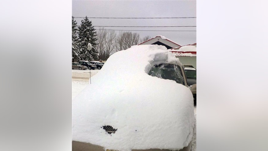 This Tuesday, Jan. 19, 2016 photo provided by the Ontario Provincial Police shows a snow covered vehicle in Brussels, Ontario. (Sgt. Russell Nesbitt/Ontario Provincial Police via AP)