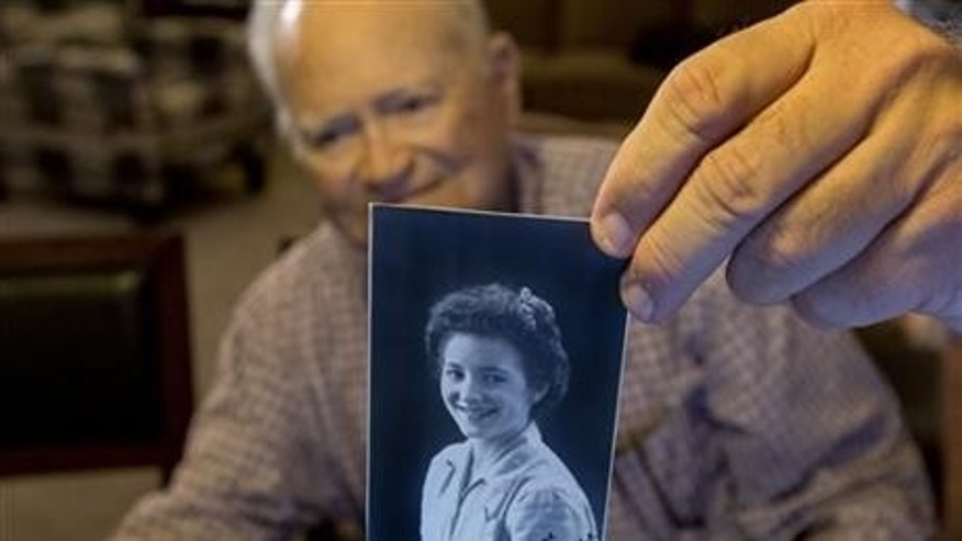 Nov. 6, 2015: Norwood Thomas, 93, holds up a photo of with Joyce Morris at his home in Virginia Beach, Va. During World War II, Morris lived in England and was Joyce Durrant, the girlfriend of Thomas, a D-Day paratrooper with the Army's 101st Airborne Division. Morris now lives in Australia. (Bill Tiernan/The Virginian-Pilot via AP)