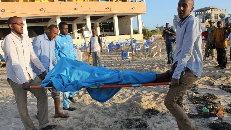 Jan. 22, 2016: Relatives carry away a dead body from the beach following an overnight attack on a beachfront restaurant in Mogadishu, Somalia.