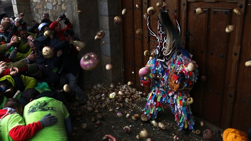 Jan. 20, 2016: People throw turnips at the Jarramplas as he makes his way through the streets beating his drum, during the Jarramplas festival in Piornal, Spain.