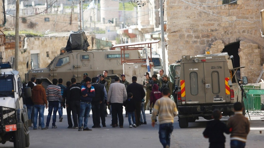 Israeli security forces stand guard as Jewish settlers are forced out of two homes in Hebron.