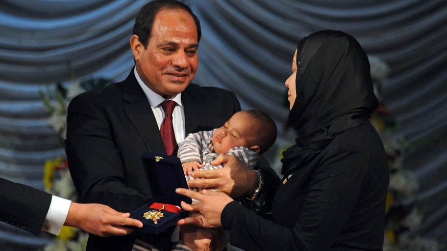 Jan. 23, 2016: In this photo provided by Egypt's state news agency, MENA, Egyptian President Abdel-Fattah el-Sissi holds a child as he presents a medal to the widow of a policeman killed in militant attacks, at a ceremony marking Police Day, which falls on Jan. 25, the anniversary of the 2011 uprising that toppled longtime ruler Hosni Mubarak, in Cairo, Egypt.