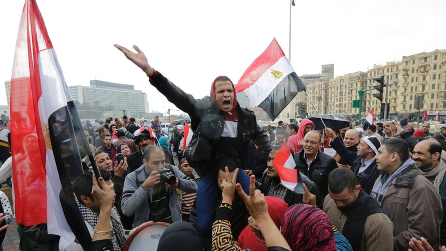 Supporters of Egyptian President Abdel Fattah el-Sissi wave national flags and shout supporting slogans Monday.
