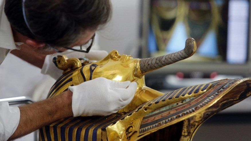 FILE - In this Tuesday, Oct. 20, 2015 file photo, German restorer Christian Eckmann begins restoration work on the golden mask of King Tutankhamun over a year after the beard was accidentally broken off and hastily glued back with epoxy at the Egyptian Museum in Cairo.  (AP Photo/Amr Nabil, File)