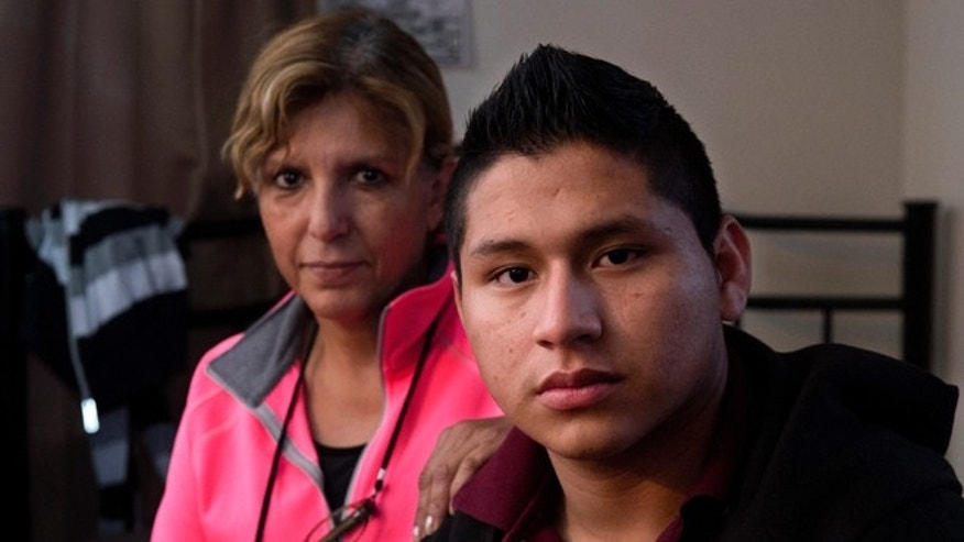 Marvin Velasco, 15, right, poses for a photo with his new sponsor, Ingrid Ainspac, at their home in Los Angeles on Monday, Jan. 11, 2016. After escaping from a previous sponsor who was abusive, he sought sanctuary in a nearby church, where he met a parishioner who took him in and became his legal guardian. He now lives with a Guatemalan immigrant family, which is raising him as a son. (AP Photo/Mark J. Terrill)