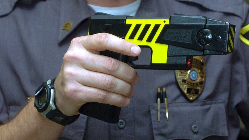 FILE - In this Oct. 28, 2004 file photo, an officer holds a stun gun used by his police department in a Farmington, Conn. Police across Connecticut disproportionately fired stun guns at blacks and Hispanics in 2015 while whites were the main beneficiaries when officers only threatened to use the weapons, according to preliminary data from the nationâs first accounting by a state of law enforcement stun gun use. State officials cautioned against making quick conclusions about the figures, saying they have just begun to analyze them after the Jan. 15, 2016 deadline for police departments to submit the reports. Civil liberties advocates also said the data appear to show racial disparities on the surface, but more analysis is needed.  (AP Photo/Bob Child, File)