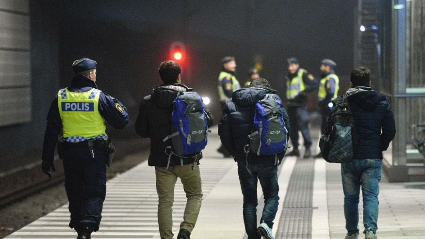 FILE - In this Dec. 17, 2015 file photo, the police escort 3 men from a train at Hyllie station outside Malmo, Sweden.