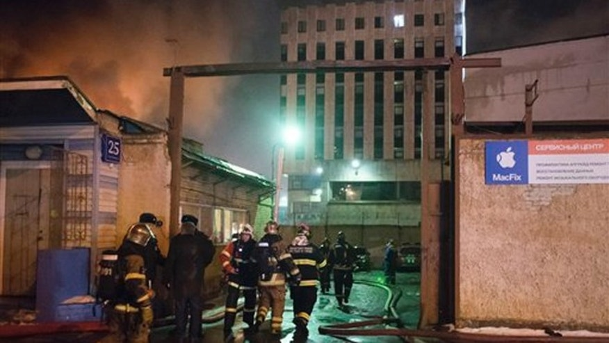 Firefighters late Saturday Jan. 30, 2016, battle fire at a textile workshop in Moscow, Russia. (AP Photo/Nikolay Koreshkov)