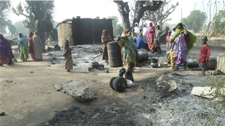Women and children look at burnt out houses following an attack by Boko Haram in Dalori village 5 kilometers (3 miles) from Maiduguri, Nigeria, Sunday Jan. 31, 2016. (AP Photo/Jossy Ola)