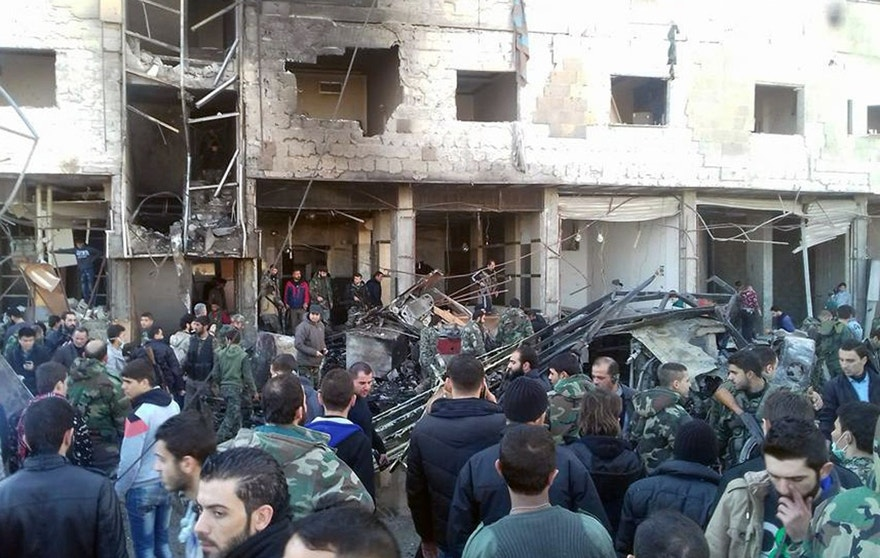 In this photo released by the Syrian official news agency SANA, Syrians gather where three bombs exploded in Sayyda Zeinab, a predominantly Shiite Muslim suburb of the Syrian capital, Syria, Sunday, Jan. 31, 2016. The triple bombing claimed by the extremist Islamic State group killed at least 45 people near the Syrian capital of Damascus on Sunday, overshadowing an already shaky start to what are meant to be indirect Syria peace talks. (SANA via AP)