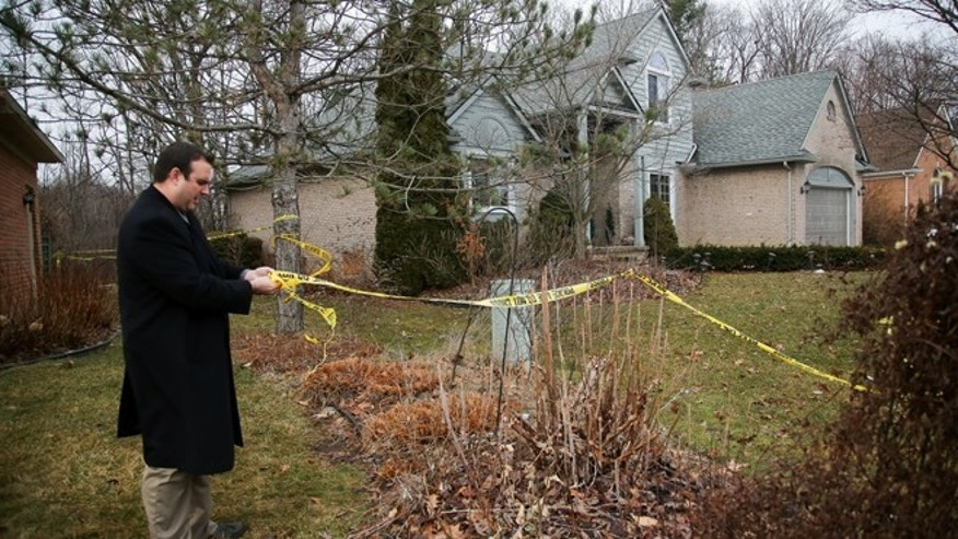 A Novi police detective secures the police tape around a home where five Mexican immigrants died in a weekend house fire, Tuesday, Feb. 2, 2016, in Detroit. (Kimberly P. Mitchell/Detroit Free Press via AP)
