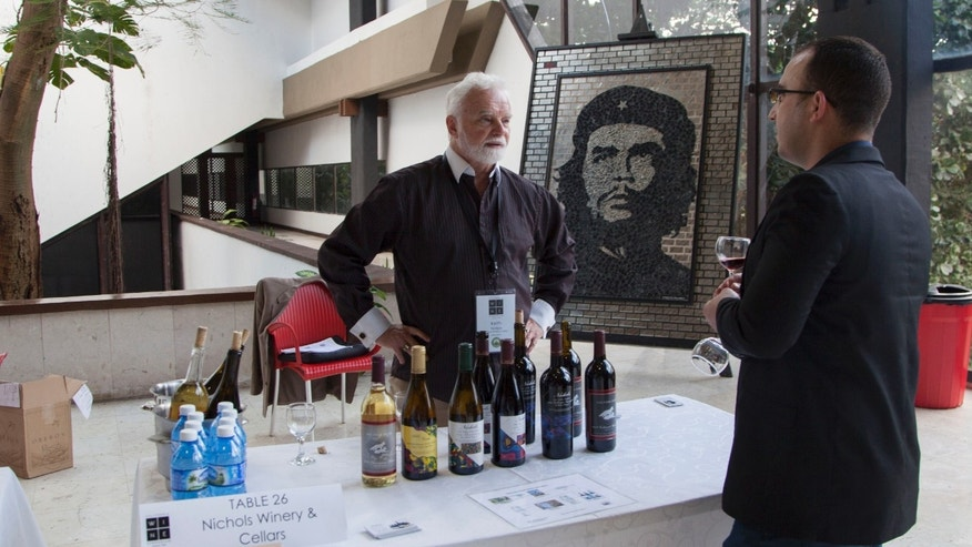 California winemaker Keith Nichols stands at a table with a selection from his winery during the first California Wine Symposium in Havana, Cuba, Tuesday, Feb. 2, 2016. About 100 California wine producers, distributors and exporters descended on Havana this week for a two-day symposium aimed at reintroducing Cuban restaurant owners and managers to the viticultural powerhouse. (Ismael Francisco/Cubadebate via AP)