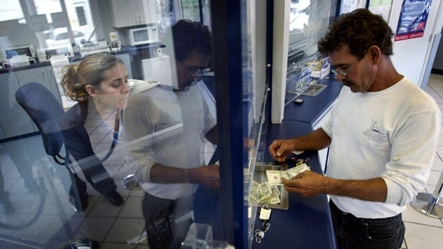MIAMI - MAY 11:  Rachel Garcia takes cash from Ramon Cruz (R) for a $300 wire transfer via Western Union to Cuba, which Cruz left three years ago, the money will be received by his mother still living on the island May 11, 2004 at a Check Cashing USA store in the Little Havana neighborhood in Miami, Florida. The Cuban government announced that many sales in U.S. dollars would be suspended indefinitely. The government blamed the new measure on the Bush Administration's decision last week to tighten trips and cash remittances to the island. (Photo by Joe Raedle/Getty Images)