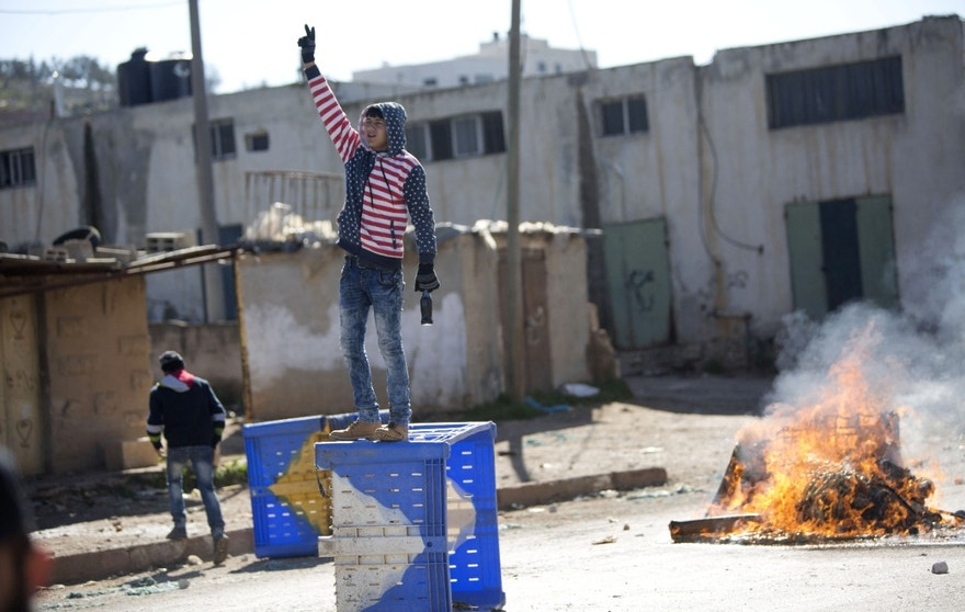A Palestinian protester stands on top of a barricade during clashes with the Israeli military in the West Bank village of Kabatiya, near Jenin, Thursday, Feb. 4, 2016. Kabatiya is the home village of the three Palestinian men who staged a deadly attack in Jerusalem on Wednesday which  killed a 19-year-old police officer and wounded another. (AP Photo/Majdi Mohammed)