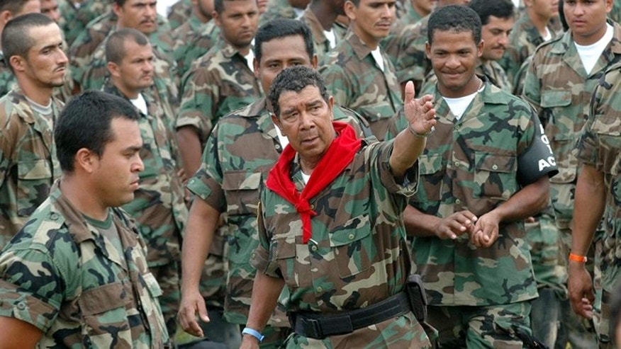 FILE - In this Feb. 7, 2006, file photo, Ramon Isaza, center, paramilitary commander of the Magdalena Medio Bloc, speaks with his men before turning in their weapons during a disarmament ceremony in Puerto Triunfo, Colombia. Officials said Friday, Feb. 5, 2016, that Isaza, who was to be released from prison on Dec. 29, 2015, after serving 10 years, was finally freed last week from a Medellin prison. (AP Photo/Luis Benavides, File)