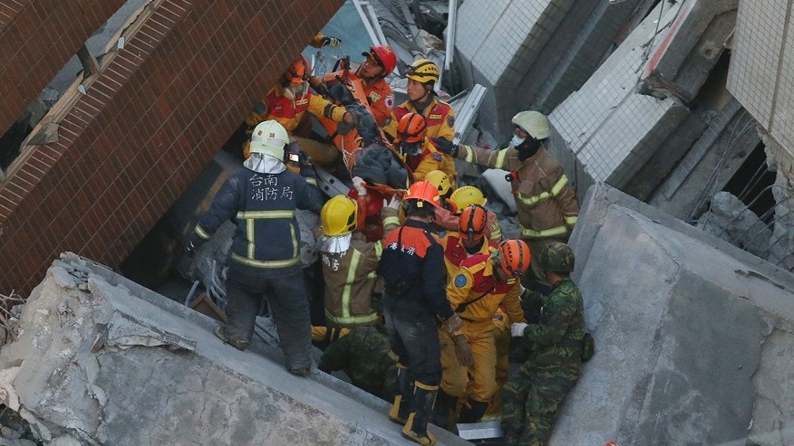 Feb. 8, 2016: Rescue workers carry a 28-year-old Vietnamese woman, identified as Chen Mei-jih, rescued from the rubble of a collapsed building complex in Tainan, Taiwan.