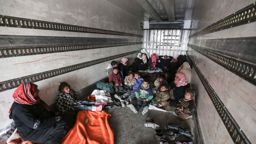 FEb. 6, 2016: Syrians gather inside a truck to protect themselves from the cold weather at the Bab al-Salam border gate with Turkey, in Syria.