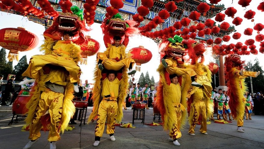 Performers participate in a lion dance at Ditan Park to mark the first day of Chinese Lunar New Year in Beijing Monday.
