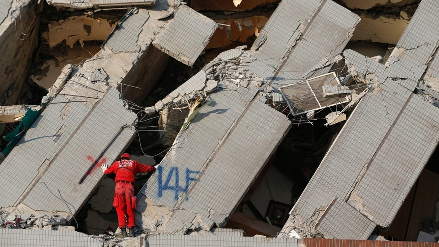 An emergency rescue worker searches what was the 14th floor of a collapsed building in Tainan, Taiwan, Sunday, Feb. 7, 2016. Rescuers on Sunday found signs of live within the remains of a high-rise residential building that collapsed in a powerful, shallow earthquake in southern Taiwan that killed over a dozen people and injured hundreds. (AP Photo/Wally Santana)