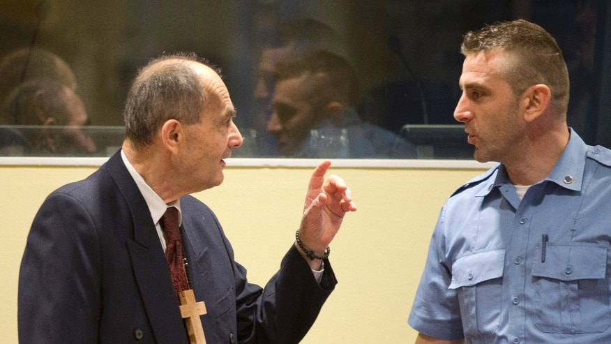 Zdravko Tolimir, left, with a U.N. security guard at the Yugoslav war crimes tribunal in 2015.