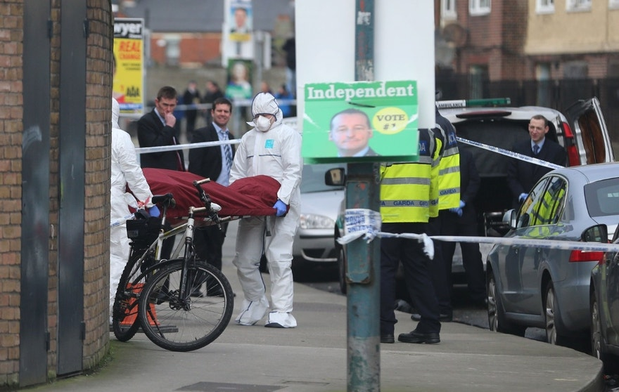 "The body of Eddie Hutch is removed from a property in Poplar Row in Dublin, Ireland, Tuesday, Feb. 9, 2016. Ireland's justice minister urged gang members to seek police protection Tuesday after gunmen shot to death the brother of a Dublin crime kingpin in apparent retaliation for last week's attack on a boxing weigh-in ceremony. Justice Minister Frances Fitzgerald spoke hours after the most brazen assault yet on the authority of Gerry ""The Monk"" Hutch, the Dublin crime figure behind many of Ireland's most daring bank heists. His faction has been blamed for Friday's attack on the hotel boxing event, where a henchman from a rival gang led by Spain-based Christy Kinahan was targeted and killed. In apparent retaliation, gunmen on Monday night broke into the Dublin home of Hutch's brother Eddie and fatally shot the 59-year-old several times in the hallway. (Niall Carson/PA via AP)    UNITED KINGDOM OUT     -    NO SALES     -      NO ARCHIVES"