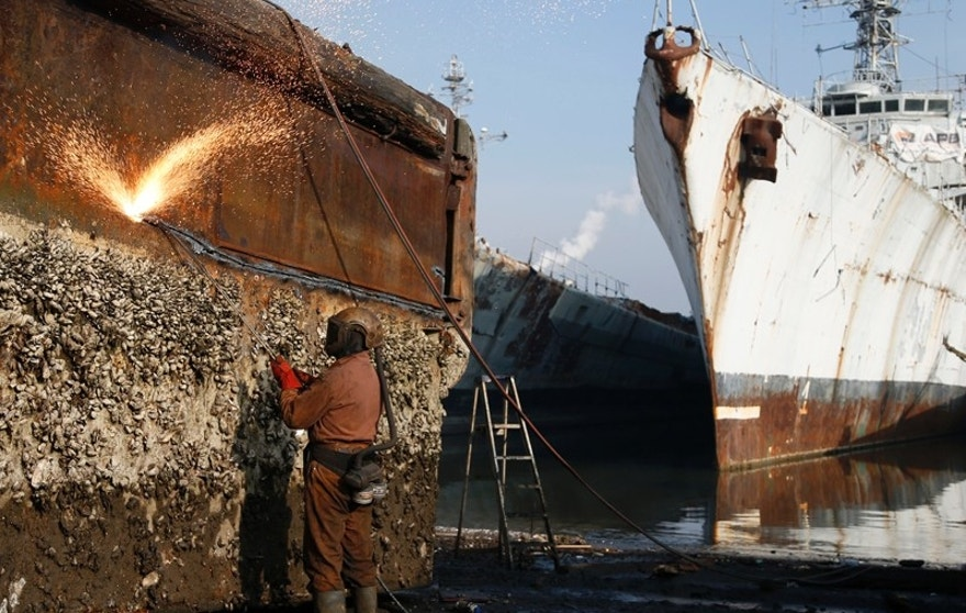 A worker uses a cutting torch to dismantle the hull of a barge covered in barnacles near French navy vessels at the Galloo ship recycling plant in Ghent March 24, 2015. The site, which is Europe's largest ship recycling plant processes some 35,000 tonnes of metal every year. The European Union plans to impose strict new rules on how companies scrap old tankers and cruise liners, run aground and dismantled on beaches in South Asia. However the practice in India, Bangladesh and Pakistan, hazardous for humans and the environment, will still be hard to stop. European, Turkish and Chinese recyclers are set to benefit from the revamped standards. Depending on raw material prices, ship owners can make up to $500 per tonne of steel from an Indian yard, compared with $300 in China and just $150 in Europe.   REUTERS/Francois Lenoir    TPX IMAGES OF THE DAY