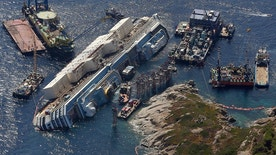 An aerial view shows the Costa Concordia as it lies on its side next to Giglio Island taken from an Italian navy helicopter August 26, 2013. The wrecked Costa Concordia cruise ship could be upright again next week, nearly two years after the liner capsized and killed at least 30 people off the Italian coast. The giant vessel, which has lain partly submerged in shallow waters off the Tuscan island of Giglio since the accident in January 2012, will be rolled off the seabed and onto underwater platforms. Picture taken August 26, 2013. REUTERS/Alessandro Bianchi (ITALY - Tags: TRANSPORT MARITIME DISASTER) - RTX13IQ3