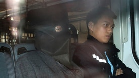 FILE - In this Jan. 25, 2016 file photo, Chinese fugitive Shi Deyun, left, escorted by a police officer in a police van, arrives at a magistrate court in Hong Kong, following his arrest after arriving on a flight from Los Angeles in connection with the slayings of his teenage nephews in Arcadia, Calif.  Shi agreed in a Hong Kong court Thursday, Feb. 11 to be sent back to the U.S. (AP Photo/Vincent Yu, File)